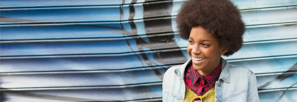 Woman with black curly hair, plaid blouse, smiling and having fun.