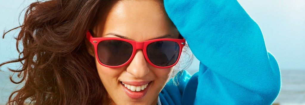 A smiling woman wearing red sunglasses, running a hand through her thick, wavy brown hair.