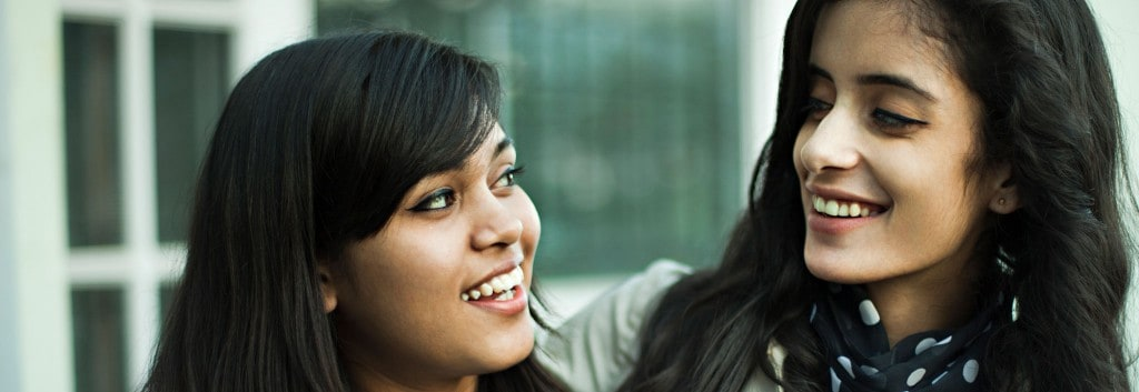 Close up of two women with thick black hair looking at each other mid-conversation.