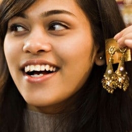 Close up of a woman trying on a new pair of earrings.