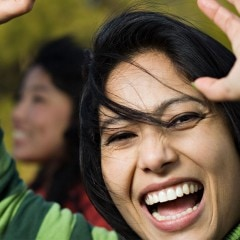 Close up of laughing woman with her hands in the air.