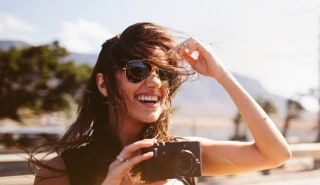 A woman standing on a beach and holding a camera, laughing as the wind blows her brown hair into her face.